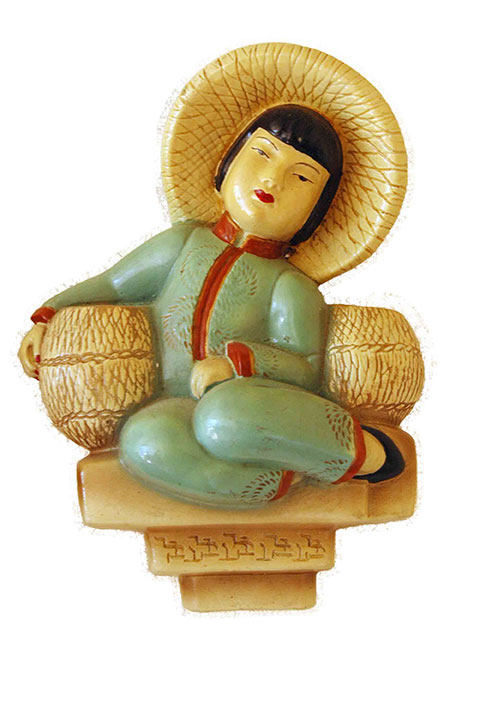 This is a piece of chalk ware that hangs on the wall. It's of a Chinese peasant girl wearing a green and red pajama suit and a rice picker's hat.