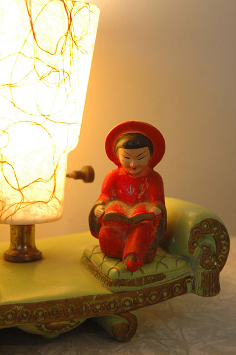 This is a 1950s chalk ware lamp. The Chinese figurine is ceramic. The lampshade is fiberglass.