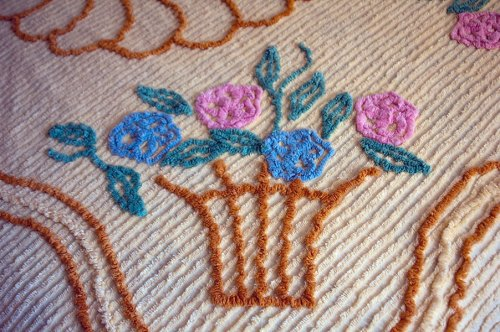 A vintage full-size chenille bedspread detail: a flower basket containing pink and blue flowers.