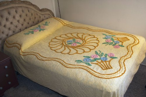 This is a picture of a full-size vintage yellow chenille bed with a design of flower baskets .